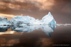Iceberg floating in the Arctic Ocean with reflections in the water.